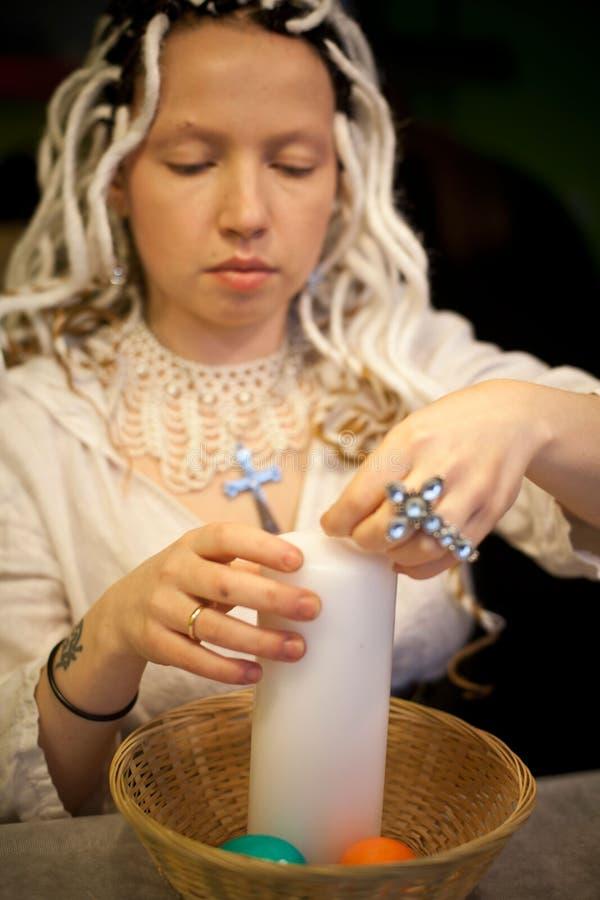 Menina com os dreadlocks brancos que guardam velas de easter imagens de stock