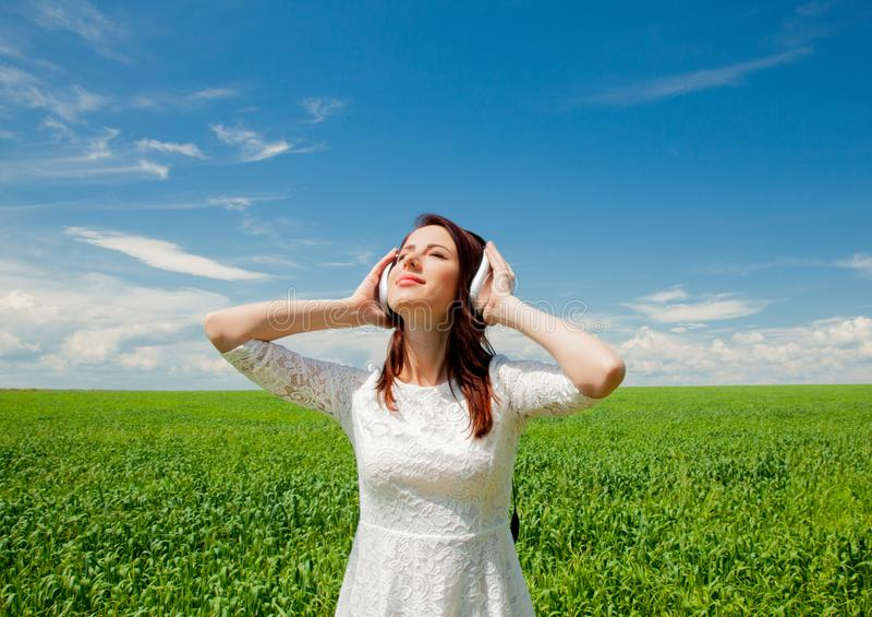 Menina com os fones de ouvido no campo de trigo imagem de stock royalty free