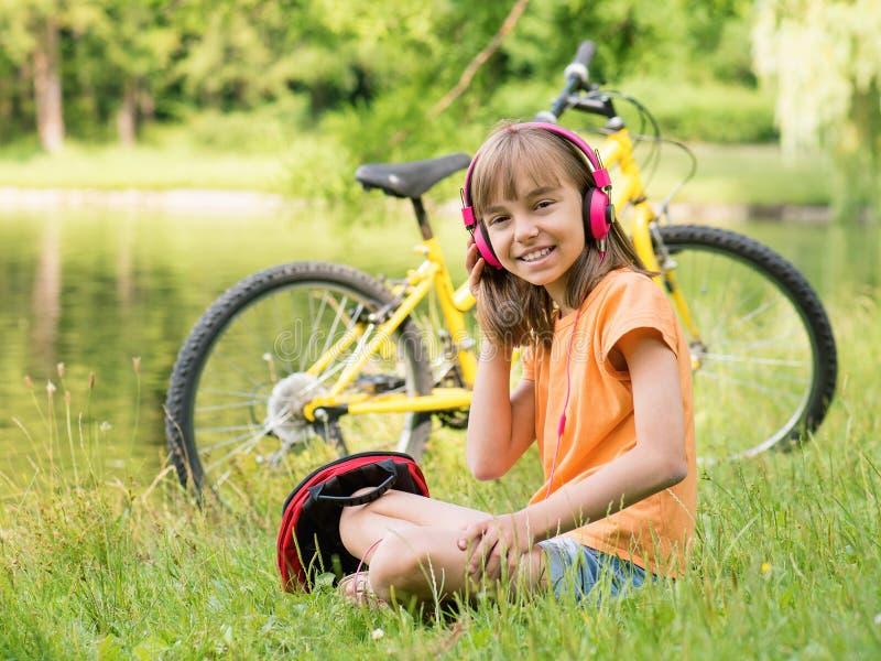 Menina com os fones de ouvido no parque fotografia de stock royalty free