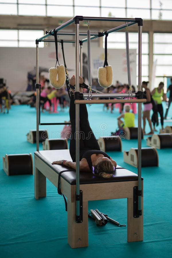 Menina com os fones de ouvido que encontram-se na cama que faz exercícios com equipamento de treino da tração dos pés no Gym fotos de stock