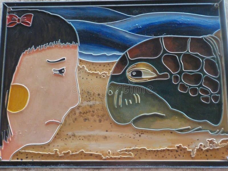 A menina com os olhos tristes e a tartaruga, Kuala Terengganu, Malásia imagens de stock