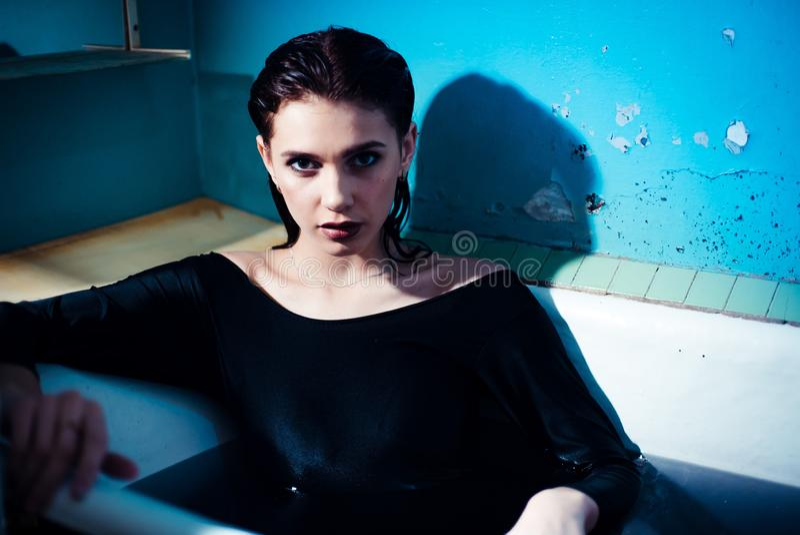 Menina com os ombros desencapados que encontram-se no banheiro com água roxa colorida Conceito da forma fotos de stock royalty free
