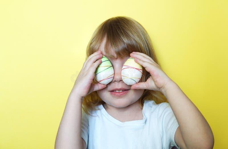 Menina com os ovos da p?scoa na frente dos olhos fotos de stock royalty free