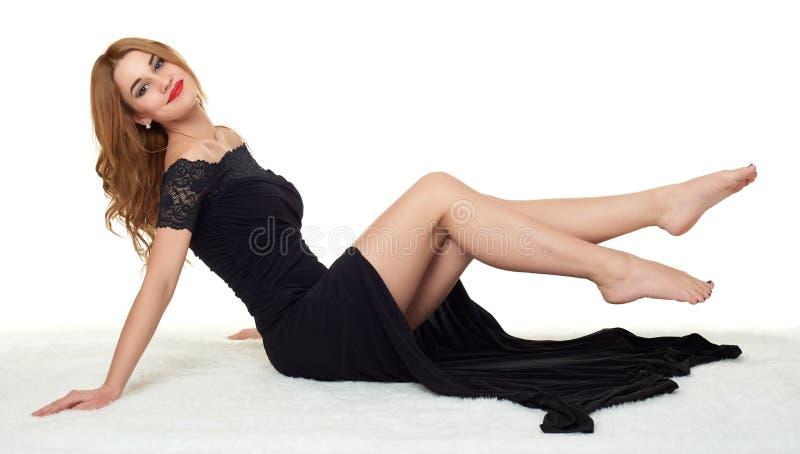 Menina com os pés desencapados que encontram-se na pele branca, vestindo um vestido preto fotografia de stock