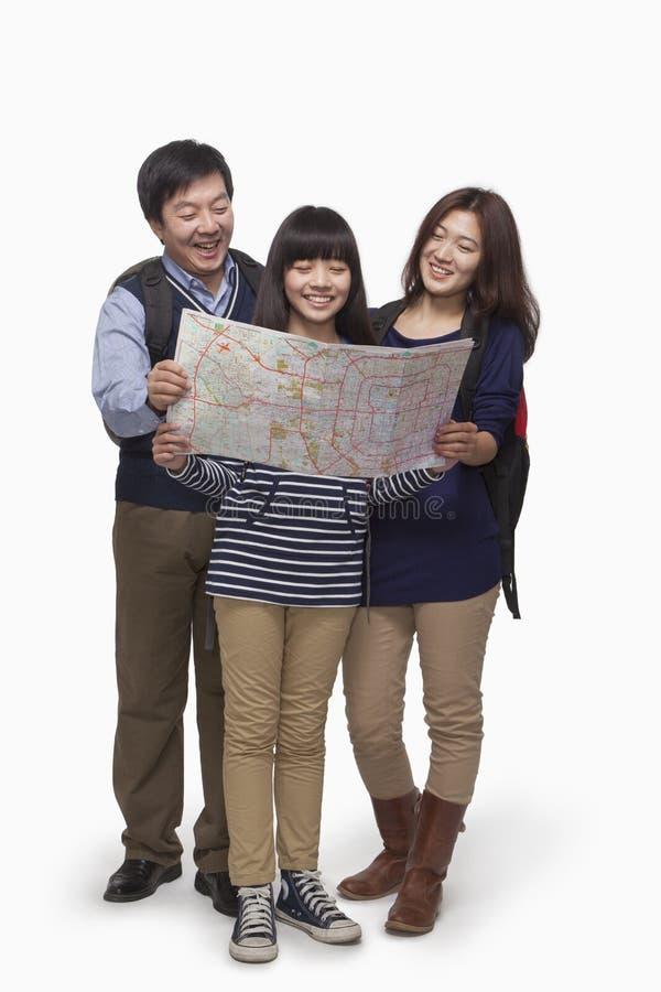 Menina com os pais que verificam o mapa fotografia de stock