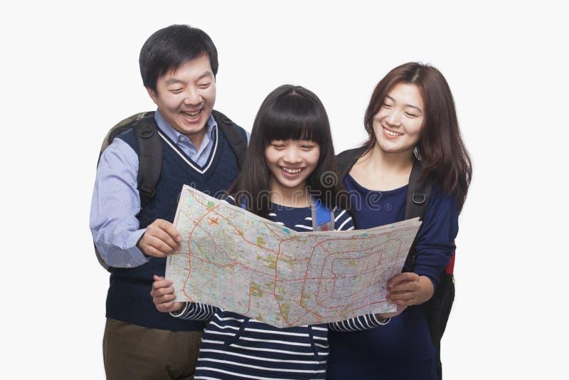 Menina com os pais que verificam o mapa fotos de stock