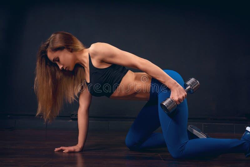 A menina com os pesos que fazem exercícios para o tríceps em meus joelhos que inclinam uma mão ao assoalho estende o braço ao lon fotos de stock