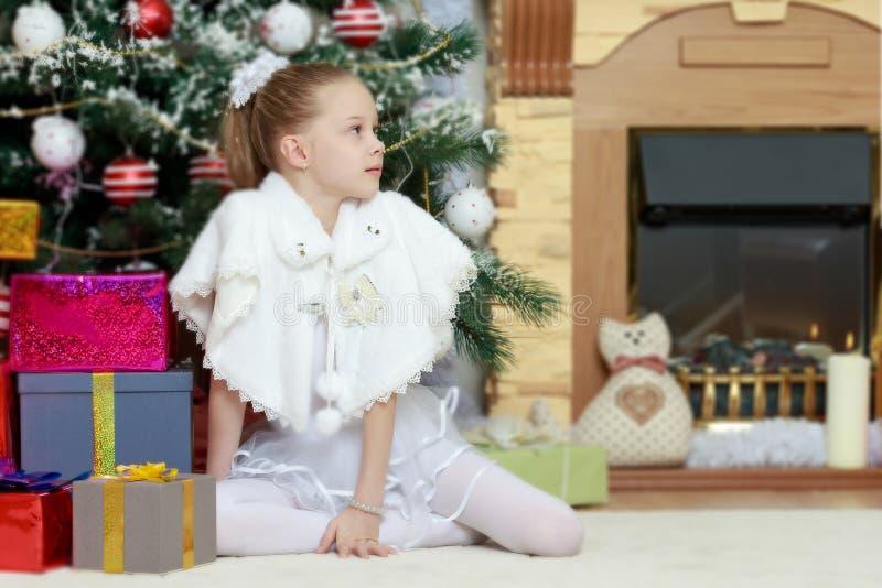 Menina com os presentes pela árvore de Natal fotografia de stock