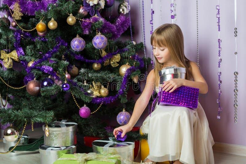 Menina com os presentes que sentam-se sob a árvore de Natal fotos de stock royalty free