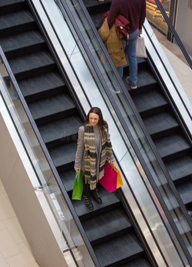 Menina com os sacos de compras na alameda foto de stock royalty free
