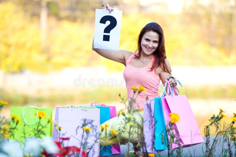 Menina com os sacos de compras que sentam-se na aleia no outono foto de stock