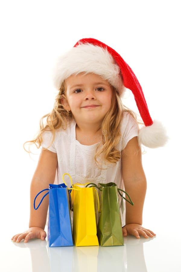 Menina com os sacos do chapéu e de compra do Natal foto de stock royalty free