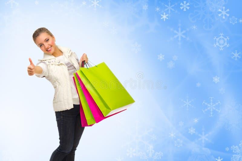 Menina com os sacos no fundo do inverno imagens de stock