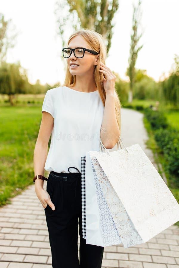 Menina com os vidros, vestidos em um t-shirt branco, guardando purchas fotos de stock royalty free
