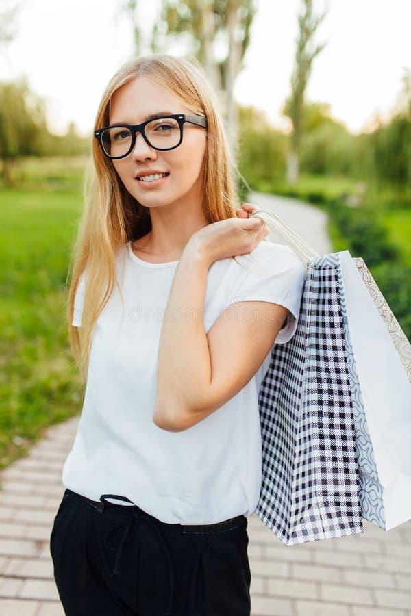 Menina com os vidros, vestidos em um t-shirt branco, guardando purchas imagens de stock royalty free