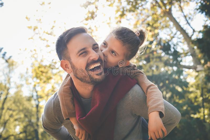 A menina com pai tem o divertimento Amor e beijos ao paizinho imagem de stock