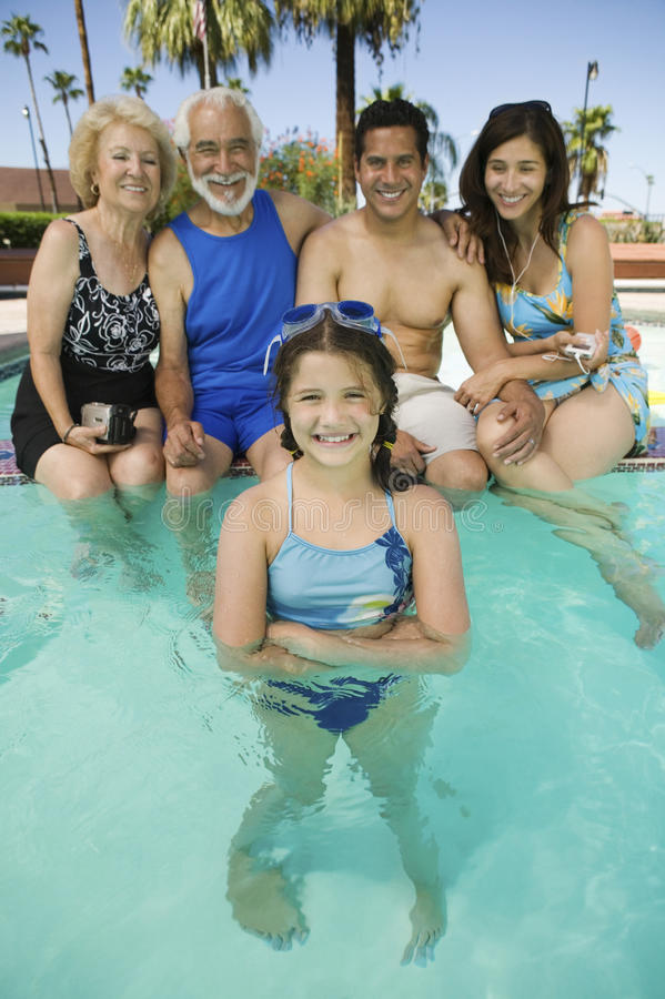Menina (10-12) com pais e avós no retrato da piscina. imagem de stock