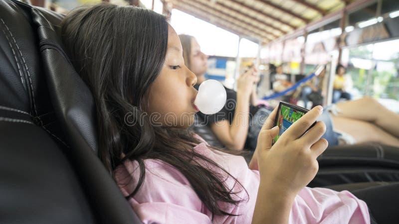 Menina com a pastilha elástica que joga o jogo no telefone fotos de stock royalty free