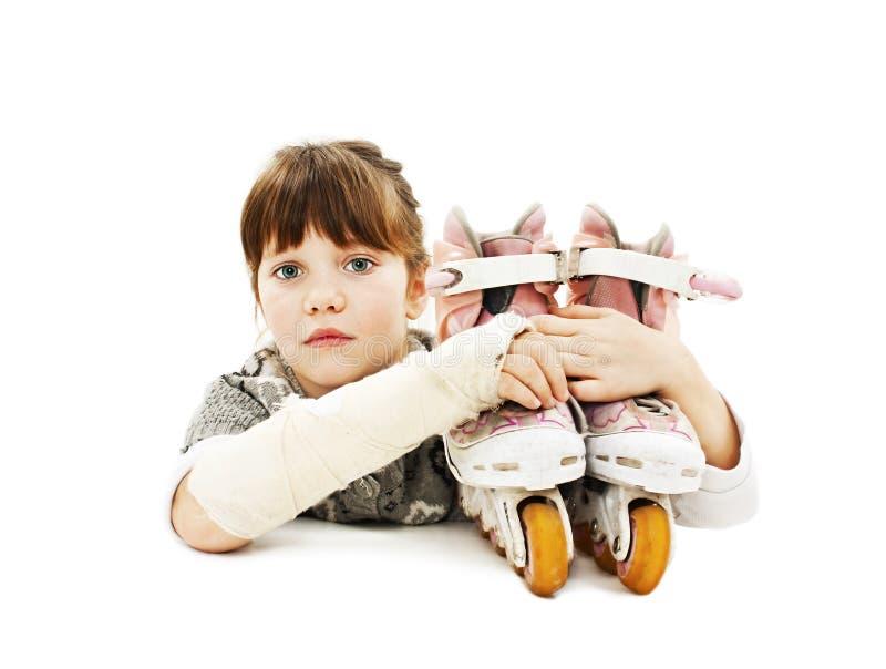 Menina com patins de rolo e o braço quebrado imagem de stock royalty free