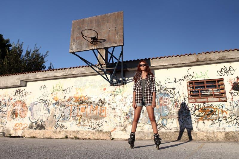 Menina com patins de rolo no fundo dos grafittis e em um basquetebol fotos de stock