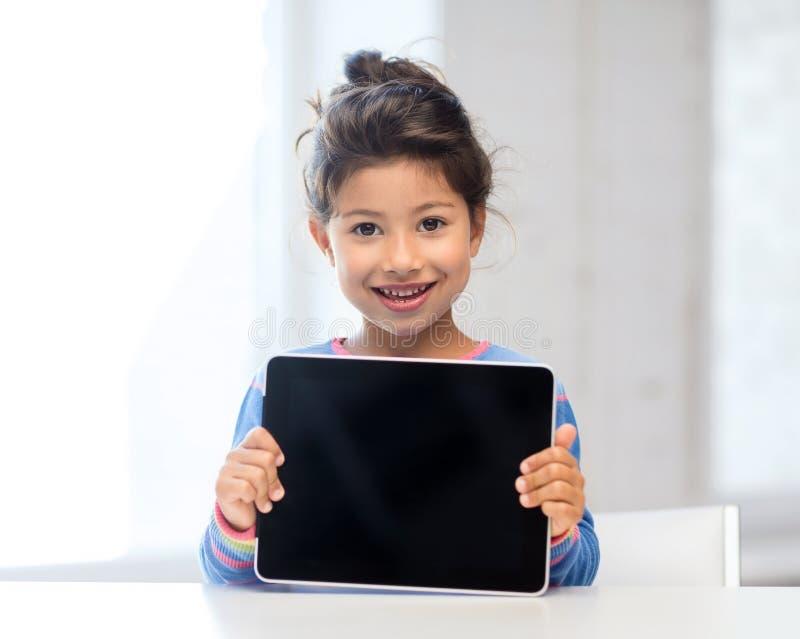 Menina com PC da tabuleta em casa foto de stock royalty free