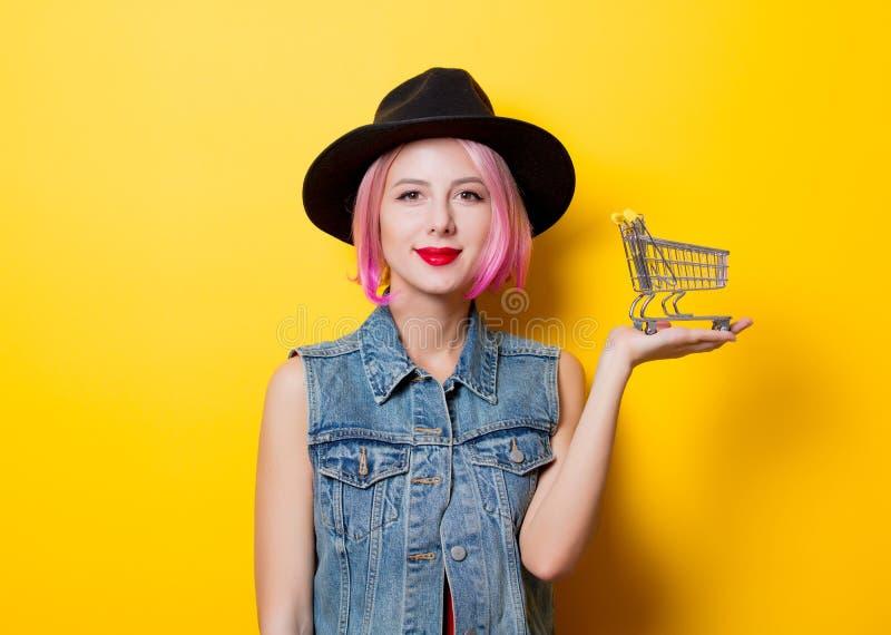 Menina com penteado cor-de-rosa com carrinho de compras foto de stock