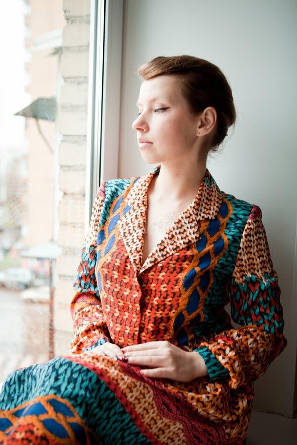 A menina com penteado retro no vestido étnico senta-se pela janela imagens de stock