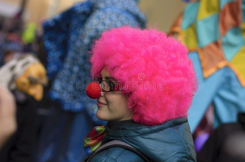 Menina com a peruca cor-de-rosa e o nariz do palhaço imagem de stock royalty free
