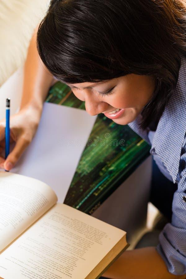 Menina com a pilha da aprendizagem de livros fotografia de stock royalty free