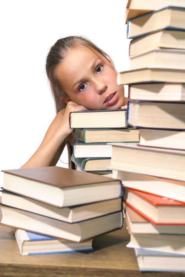 Menina com a pilha dos livros imagem de stock