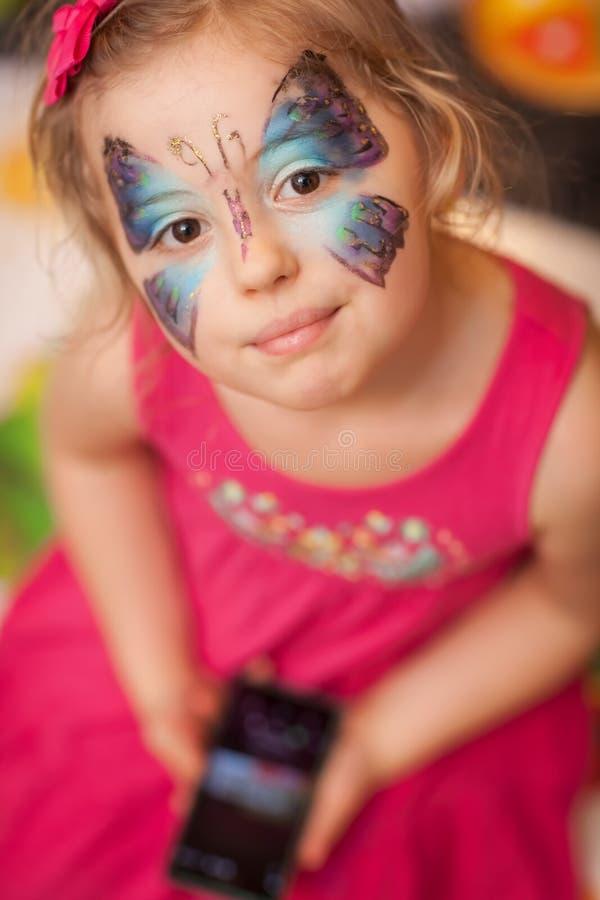 Menina com pintura da cara da borboleta fotografia de stock royalty free
