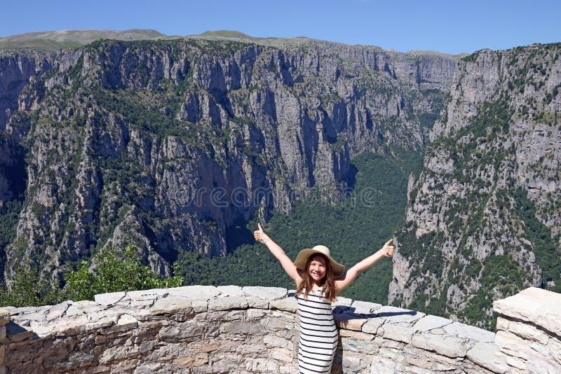 Menina com polegares acima no desfiladeiro GR de Vikos do ponto de vista fotografia de stock royalty free