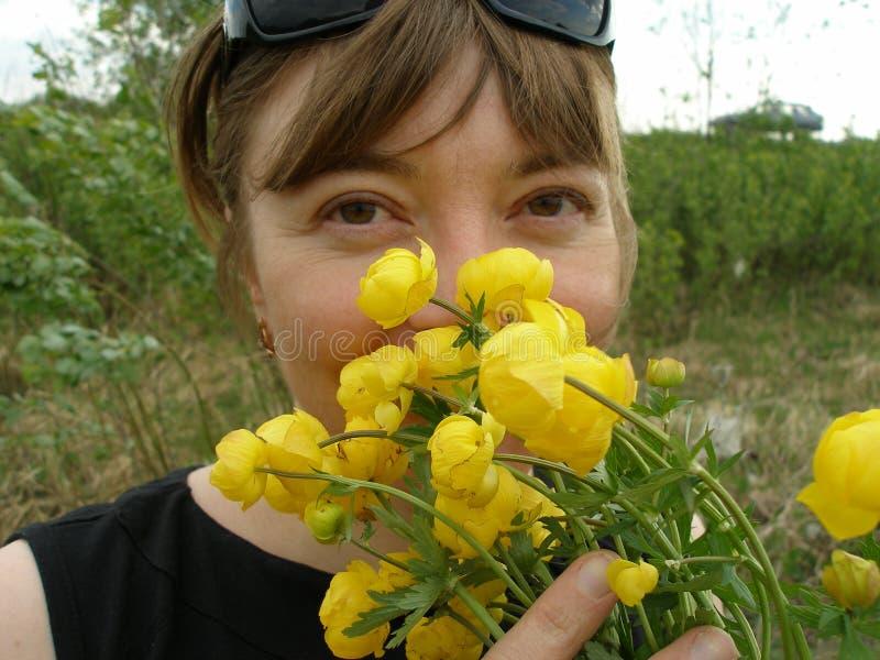 A menina com a primeira mola floresce o primeiro de maio dos globeflowers imagens de stock