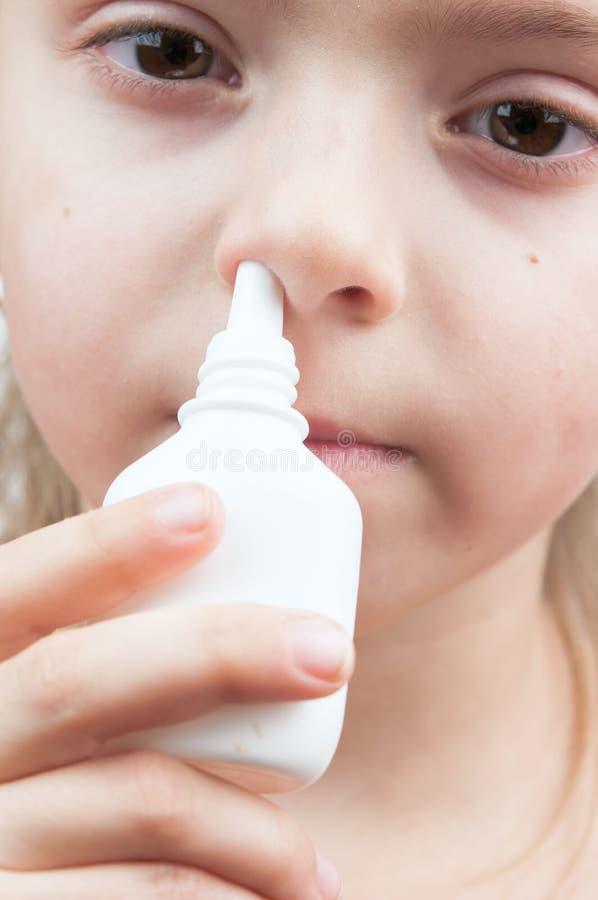 Menina com pulverizador de nariz fotografia de stock