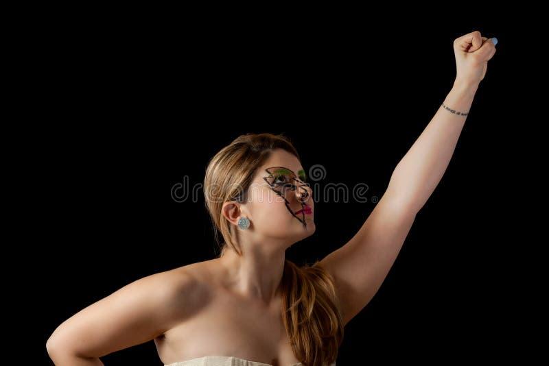 A menina com punho acima no voo do cabelo gosta do super-herói foto de stock