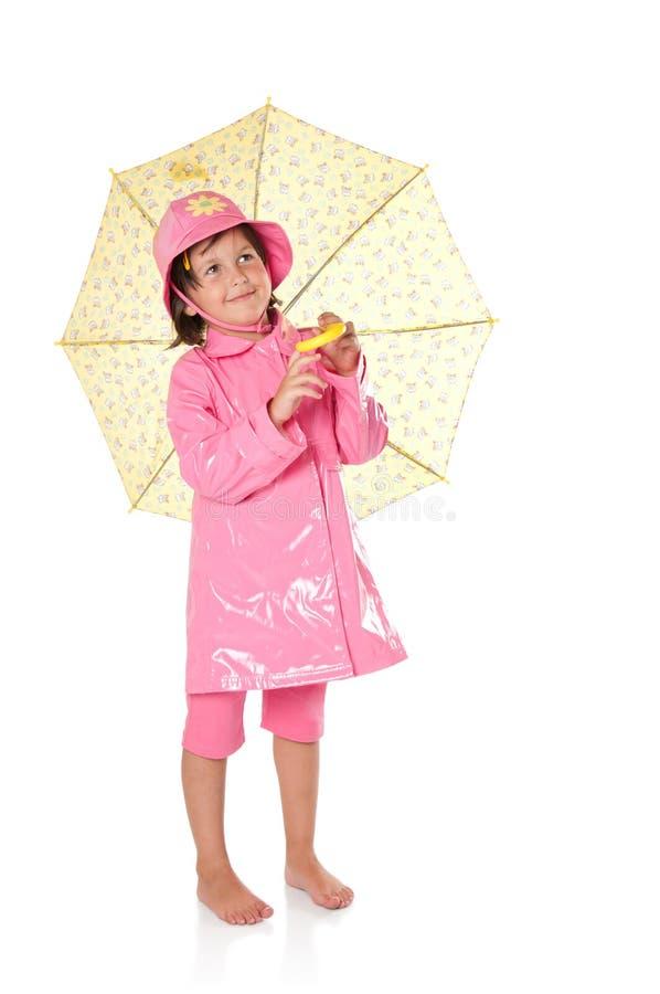 Menina com raincoat e guarda-chuva fotos de stock
