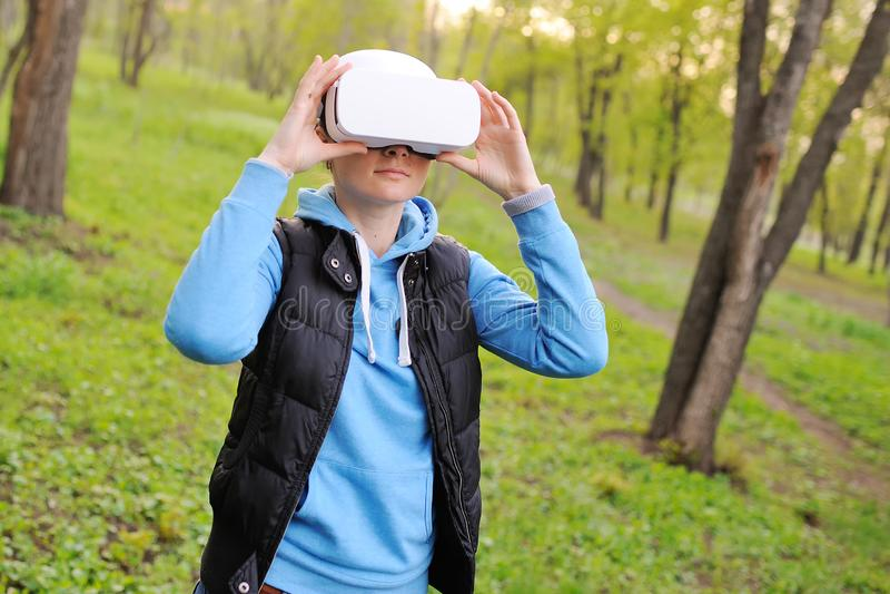 Menina com realidade virtual dos vidros no fundo das hortali?as e do parque foto de stock