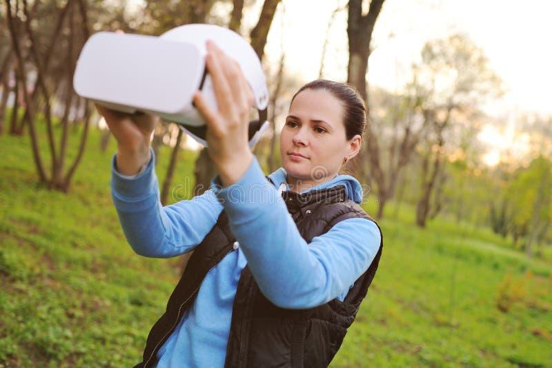 Menina com realidade virtual dos vidros no fundo das hortali?as e do parque imagens de stock