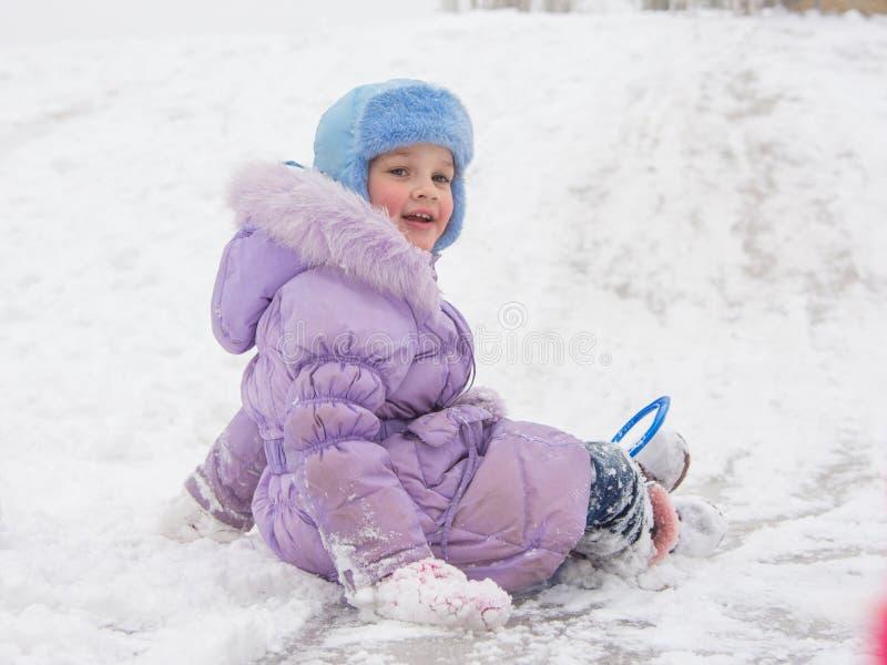 Menina com Rolling Hills coberto de neve para trás imagem de stock