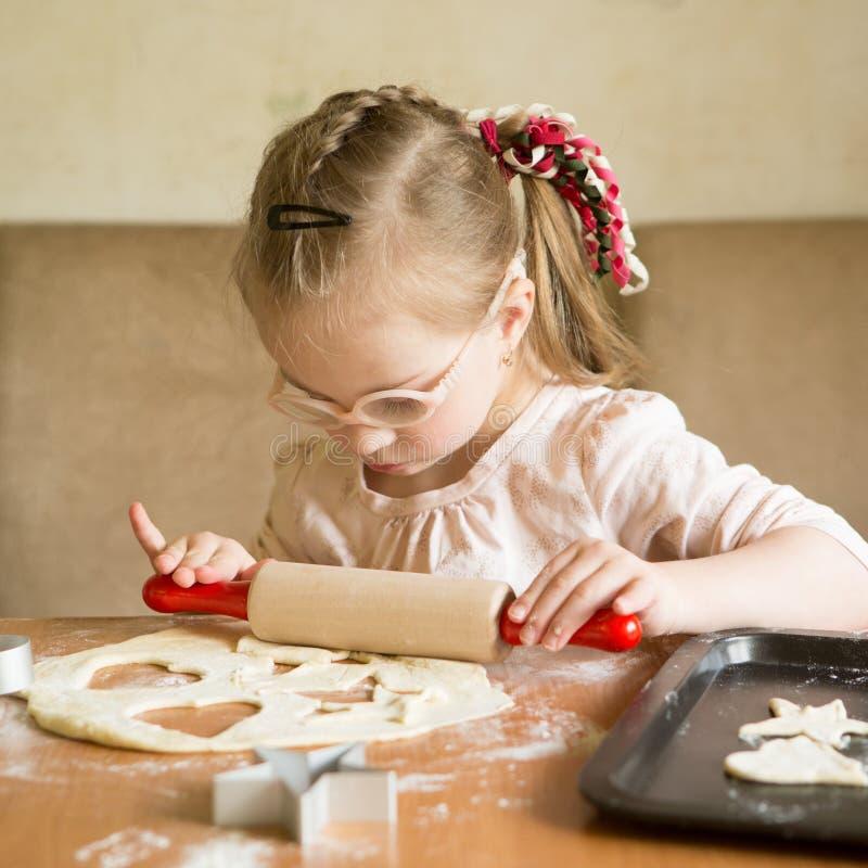 A menina com Síndrome de Down rola a massa no biscoito foto de stock