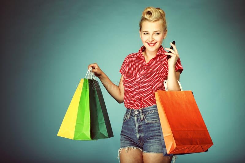 Menina com sacos de compras e estilo retro do telemóvel fotos de stock royalty free