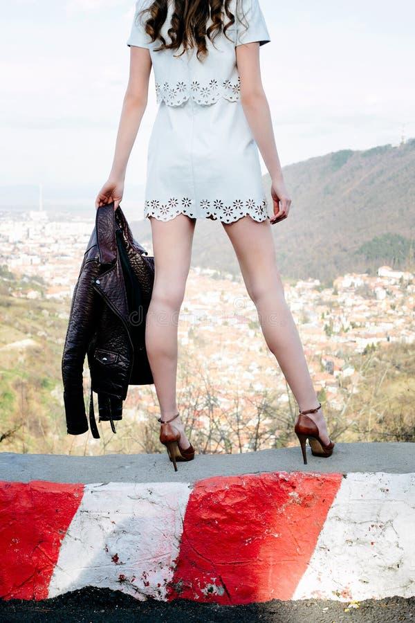 A menina com saltos altos, a saia branca curto e o casaco de cabedal preto em sua mão, olha sobre sua cidade fotografia de stock