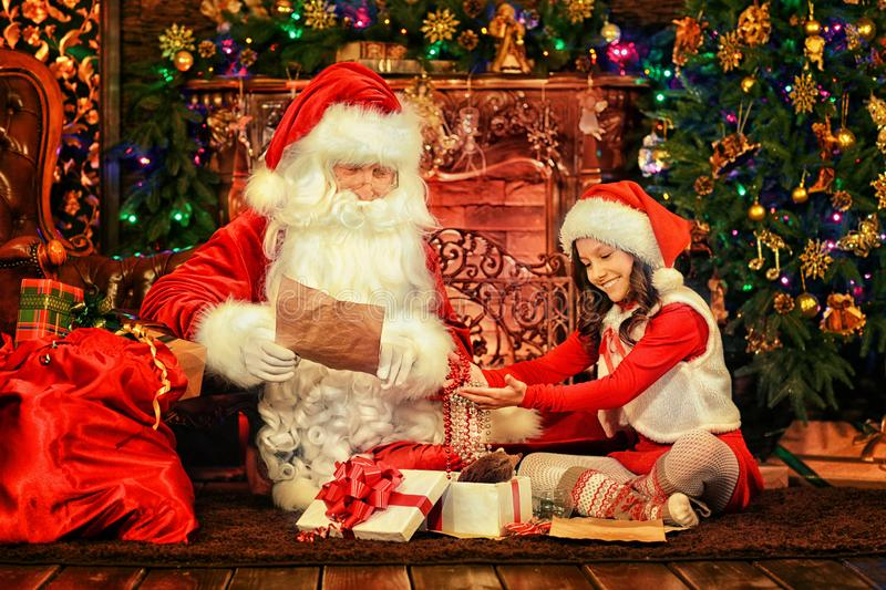 Menina com Santa Claus na sala foto de stock