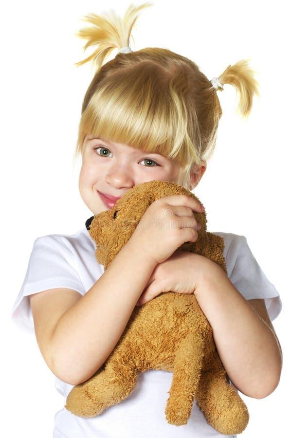 Menina com seu brinquedo do filhote de cachorro foto de stock