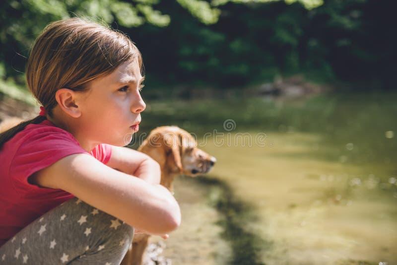 Menina com seu cão pelo lago imagem de stock royalty free