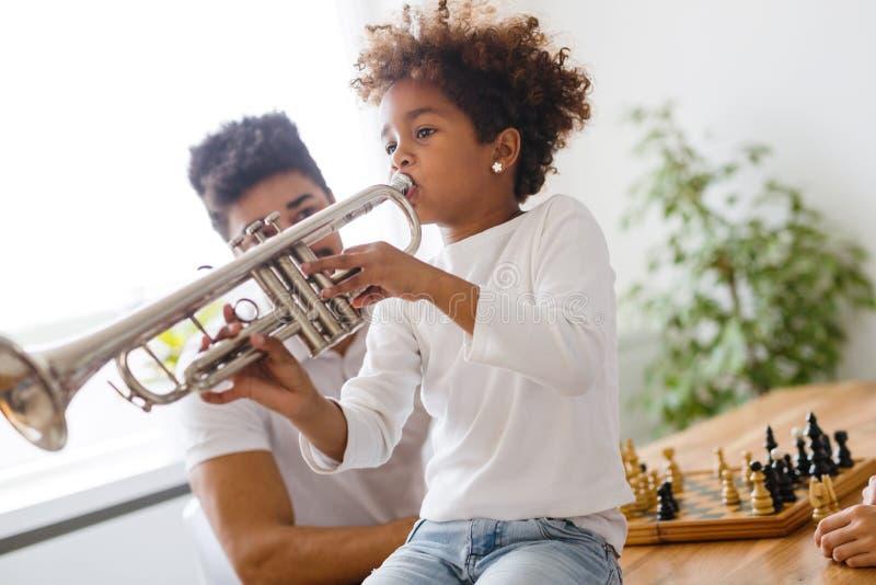 Menina com seu pai que aprende a trombeta fotos de stock royalty free