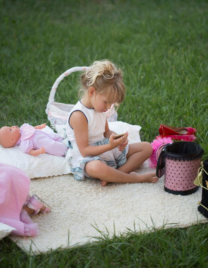 A menina com smartphone senta-se na tampa na grama verde foto de stock