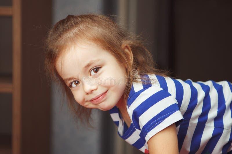 A menina com sorriso alegre está em seus mãos e pés fotografia de stock royalty free