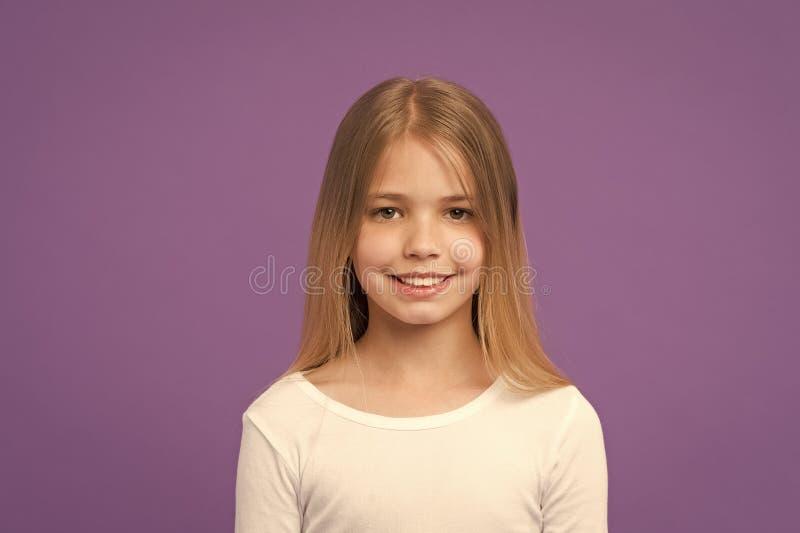 Menina com sorriso bonito isolada no fundo roxo Criança com o retrato bonito do estúdio da cara Modelo com o brilho louro imagem de stock