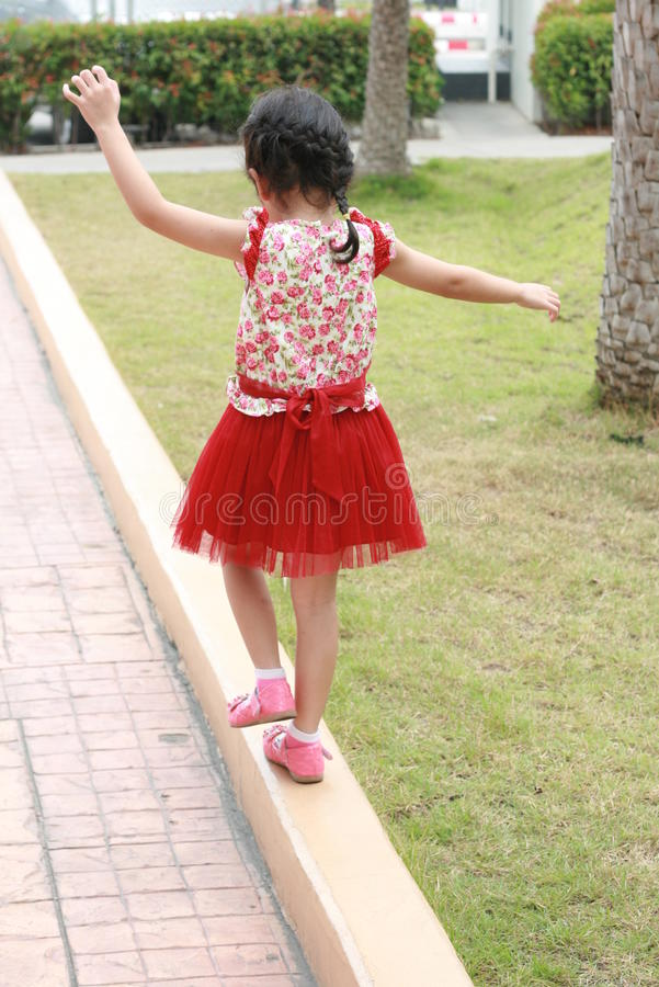 Menina com sua boneca em um jardim foto de stock